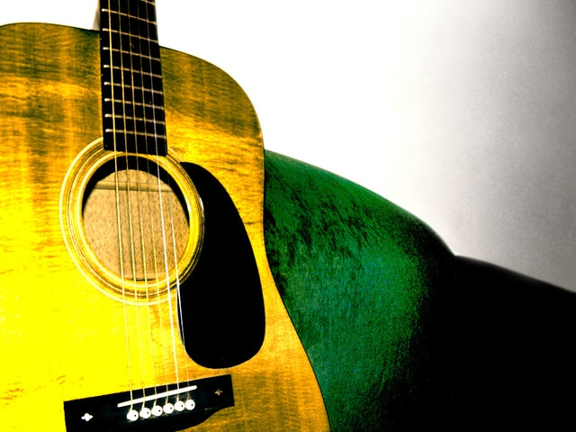 acoustic-guitar-on-green-sofa-1544514-640x480