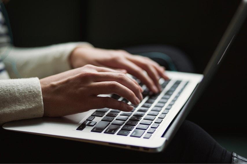 ノートPCでタイピングしている人