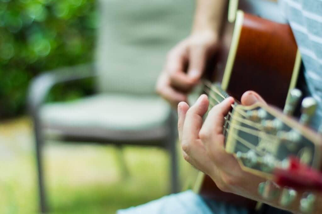 アコースティックギターを弾いてる男性