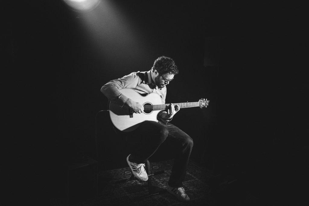 アコースティックギターを演奏する人