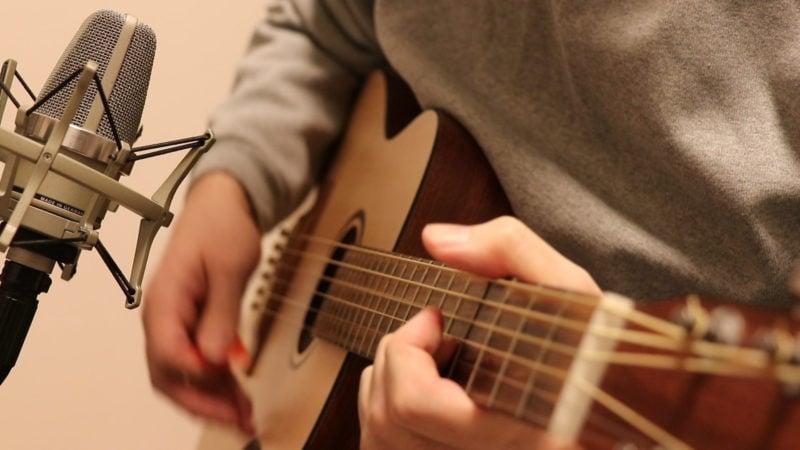 コードを押さえてギターを弾いているところ