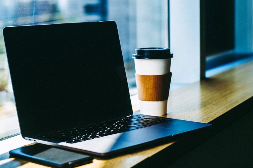 窓際のノートPCとコーヒー