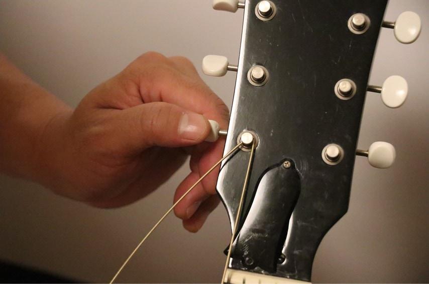 弦の先端をブリッジ側に引っ張りながら巻く