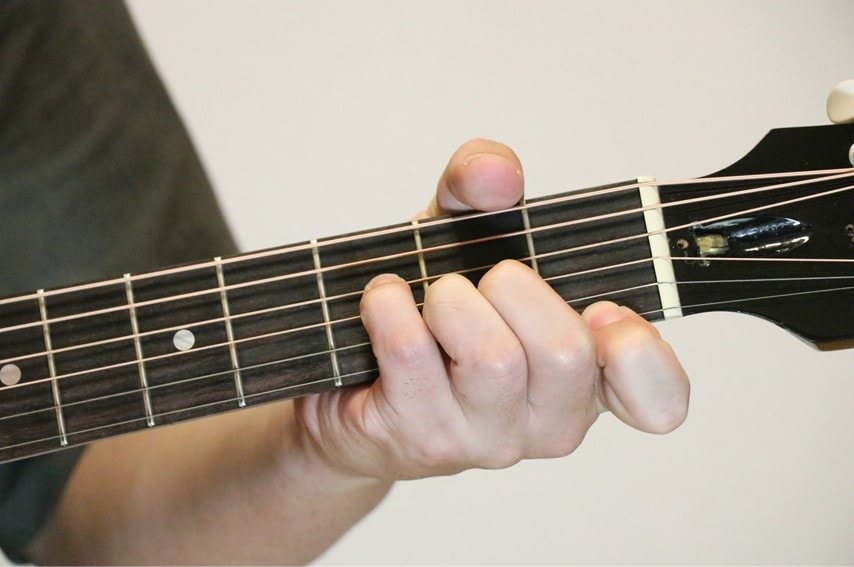 ギターでAaugコードを押さえているところ