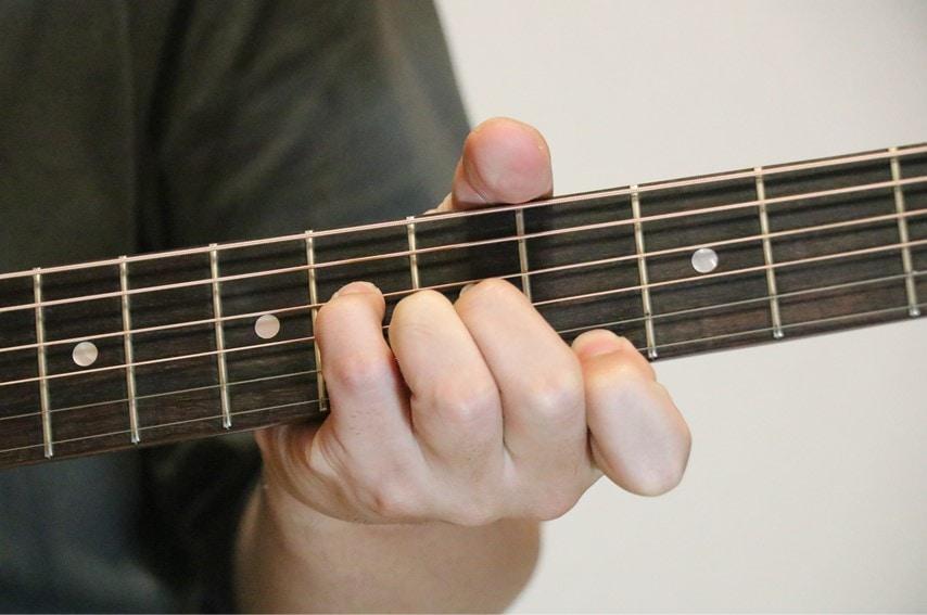 ギターでA♭augコードを押さえているところ
