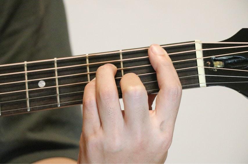 ギターでB♭mコードを押さえているところ