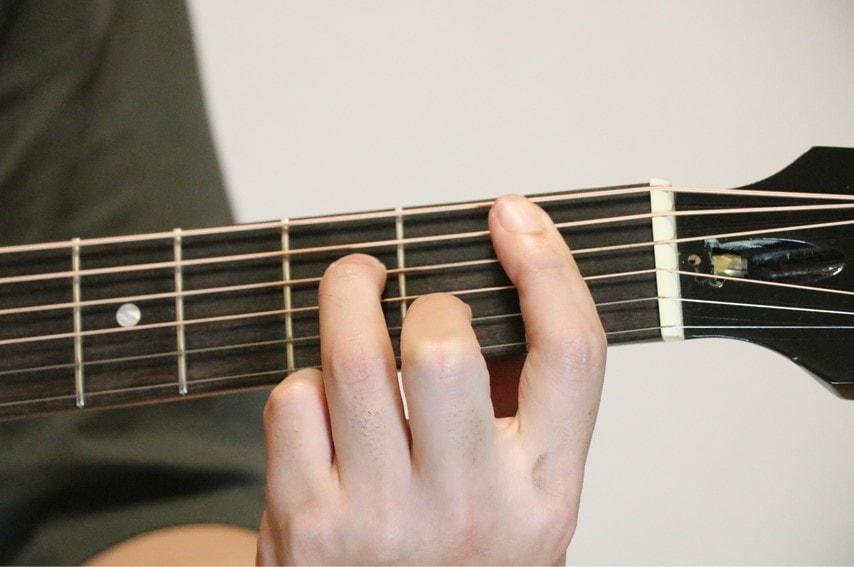 ギターでB♭m7コードを押さえているところ
