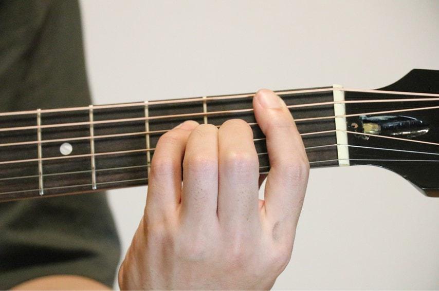 ギターでB♭mM7コードを押さえているところ