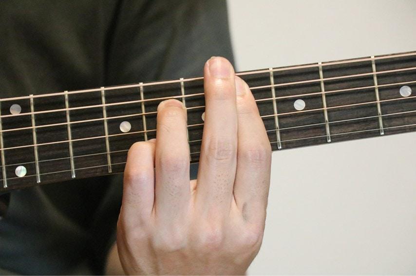 ギターでE♭7コードを押さえているところ