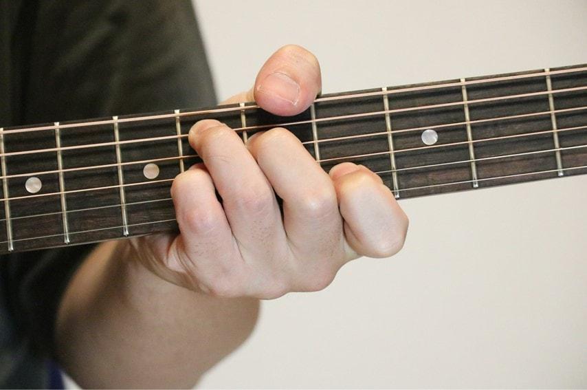 ギターで簡単なE♭7コードを押さえているところ