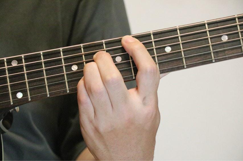 ギターでE♭コードを押さえているところ