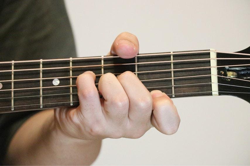 ギターでG♭augコードを押さえているところ