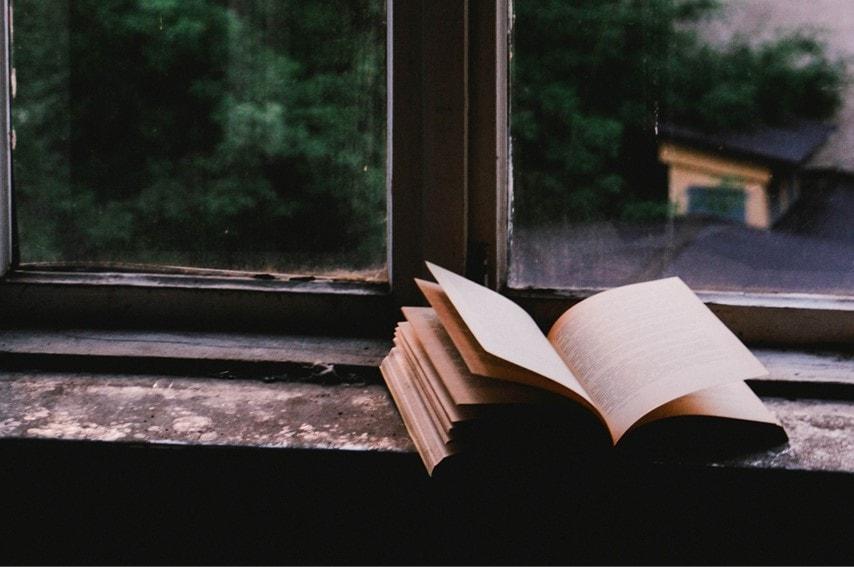 窓際で本を開いている画像