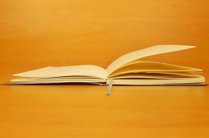 本を机に置いて開いてる写真